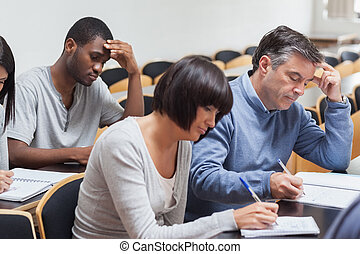 Students taking lecture notes - Mature students taking...