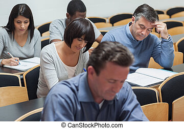 Students working in lecture hall - Mature students working...