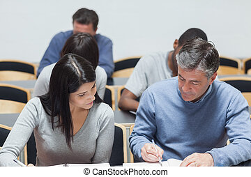 Man explaining to woman something on notepad in lecture hall...