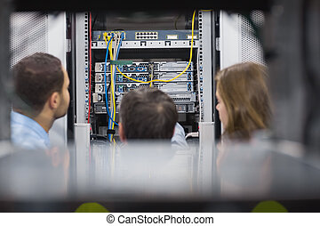 Technicians viewing a server while standing in hallway
