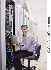Man working on laptop to check servers
