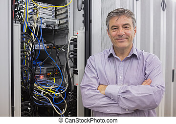 Smiling technician with arms crossed in front of server in...