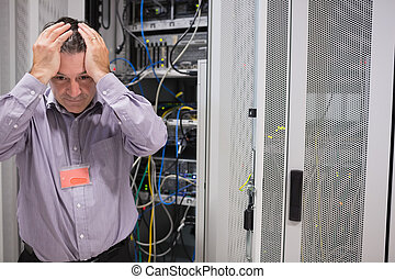 Man looking weary of data servers in data center