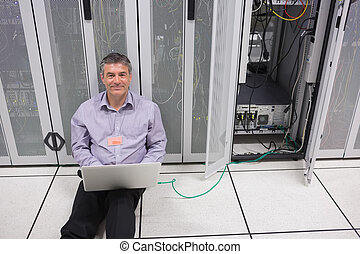 Smiling man doing server maintenance with laptop sitting on...