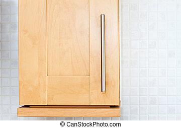 beech wooden kitchen cupboard in a white kitchen