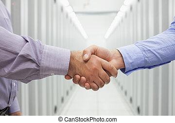 Men shaking hands - Two men shaking hands in the hallway of...