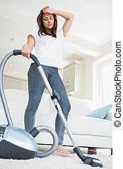 Tired woman with vacuum cleaner
