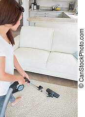 Woman cleaning the carpet with a vacuum cleaner