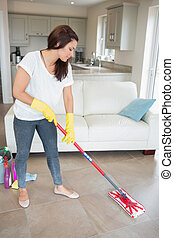 Woman mopping the living room floor of her home