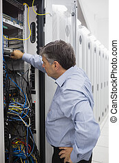 Technician working on a case of server racks - Technician...