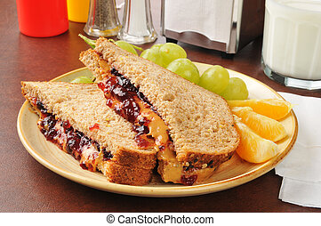 Peanut butter and jelly sandwich with fruit - A peanut...