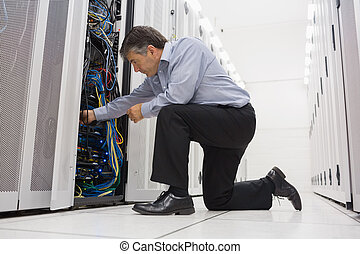 Technician kneeling and repairing a server with his hands -...