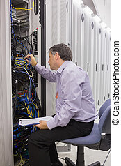 Technician with a clipboard checking servers