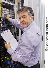 Data center worker checking the servers and holding...