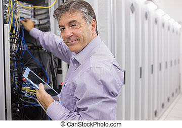 Technician using tablet pc to check the servers in data...