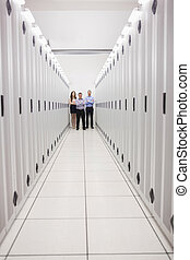 Technicians standing at end of server corridor