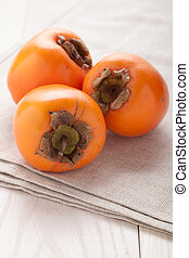 Exotic tropic orange fruits persimmon served textile towel -...