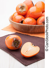 Exotic tropic orange fruits persimmon served in wooden plate...