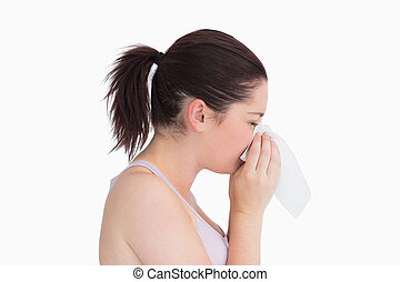 Sick woman blowing her nose against white background