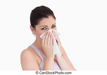 Sad woman blowing her nose against white background