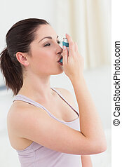 Brunette using asthma inhaler in living room