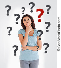 Curious woman on white background with question marks