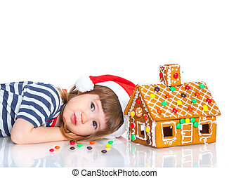 Little girl in Santa's hat with gingerbread house -...