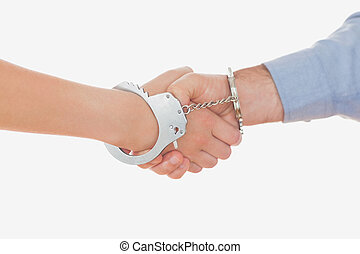 Handcuffed business people shaking hands - Close-up of...