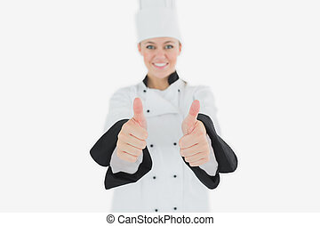 Happy female chef gesturing thumbs up - Portrait of happy...