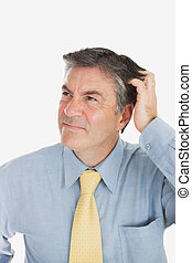 Confused businessman scratching head - Confused mature...