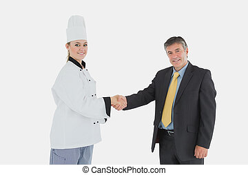 Happy businessman and female chef shaking hands - Portrait...