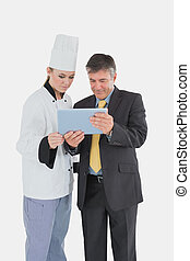 Female chef and businessman using digital tablet over white...