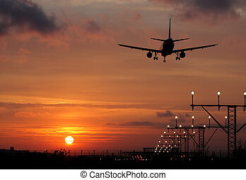 Plane landing in a sunset. Backlight