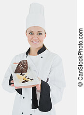 Happy young chef holding plate of pastry - Portrait of happy...