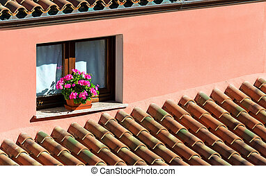 windowsill with flowers surrounded by roof tiles