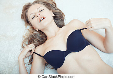 Pleasure - Blond lady laying on the bed and taking pleasure