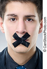 Freedom of speech - Portrait of young man with black X tape...