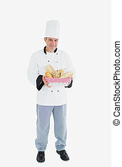 Male chef holding bread basket