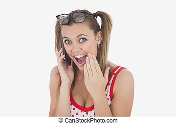 Amazed young woman using cell phone