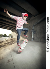 Skateboarder under overpass flipping his board