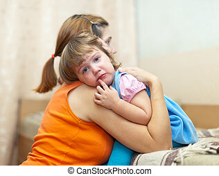 woman soothes crying daughter Focus on child