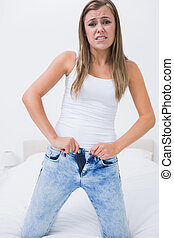 Discouraged woman trying to close her jeans on the bed