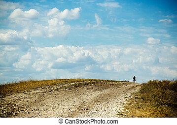 Backpacker - Traveler on foot on the road.
