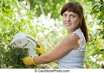 farmer composting grass - Female farmer composting grass in...