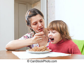 mother feeding her 2 years child at home Focus on woman