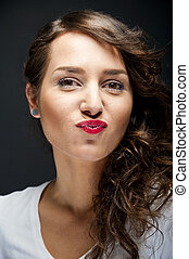 Woman with sensual kiss smile on black background