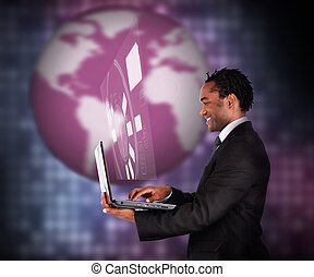 Smiling businessman using laptop against a background