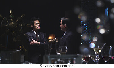 businessmen in conversation - 2 Chinese business persons in...