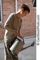 Boy with watering-pot - Boy with big metal watering-pot...