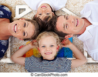 Smiling young family in front of house illustration -...